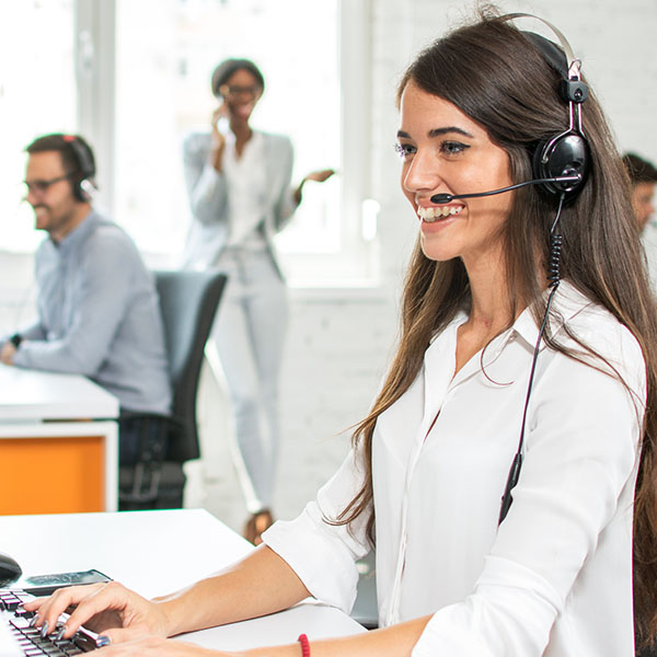 An IT support technician with a telephony headset on discussing Microsoft 365 with a client.